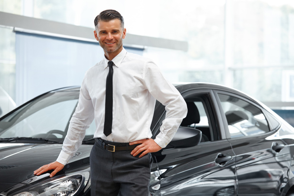 Salesman Stands Near Brand New Car. Car Showroom